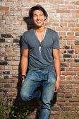Městské Asiat. Krásné. cool chlapík. na sobě šedou košili a klobouk a džíny. stojící před cihlová zeď