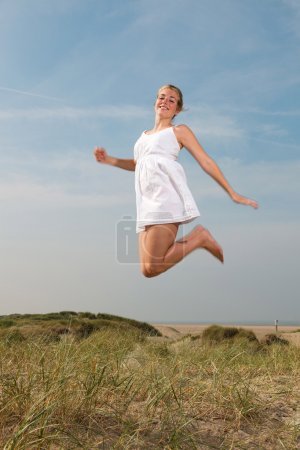 Pretty girl with red long hair wearing white dress enjoying nature near the beach. Jumping in the air. Hot summer day with blue cloudy sky.