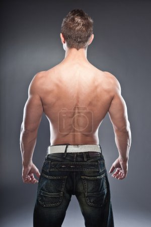 Photo for Shirtless muscled fitness man showing his back. Cool looking. Tough guy. Blue eyes. Blond short hair. Wearing black sunglasses. Tanned skin. Studio shot isolated on grey background. - Royalty Free Image