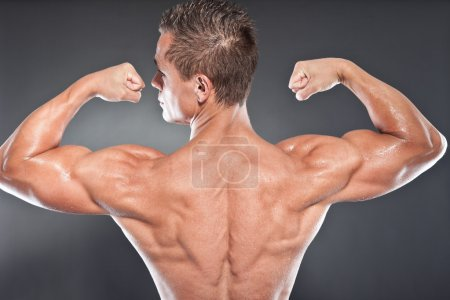 Shirtless muscled fitness man showing his back. Cool looking. Tough guy. Blue eyes. Blond short hair. Tanned skin. Studio shot isolated on grey background.