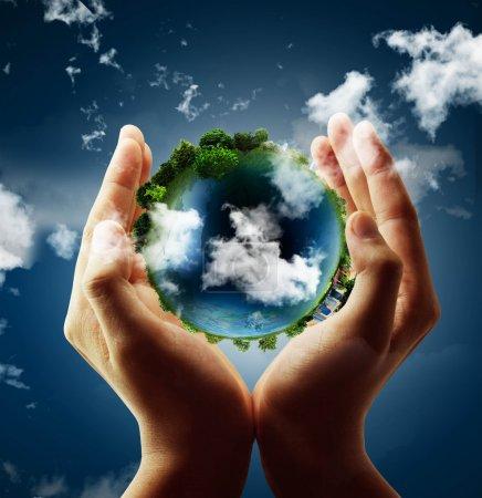 Photo pour Tenant un globe terrestre lumineux à la main - image libre de droit