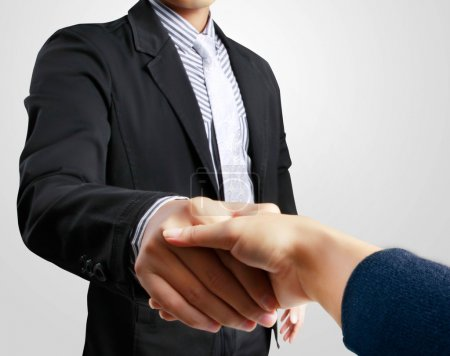 Photo for Business woman shaking hands with a man on gray background - Royalty Free Image