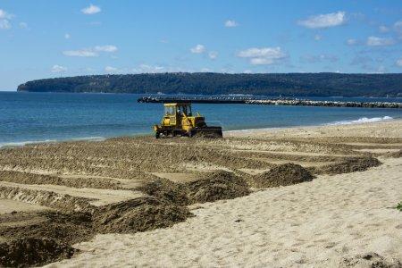 The bulldozer levels sand on a beach
