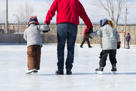 Family having fun at the outdoor skating rink in w...