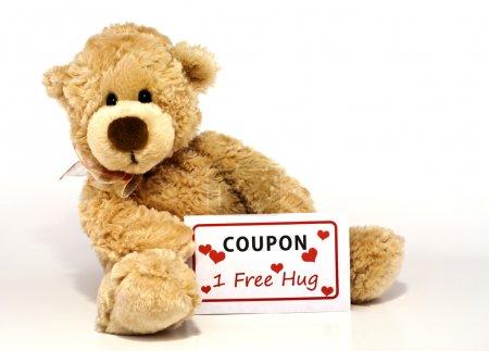 Photo pour Mignon ours en peluche brun poilu assis et tenant un coupon pour un câlin gratuit isolé sur fond blanc avec espace de copie . - image libre de droit