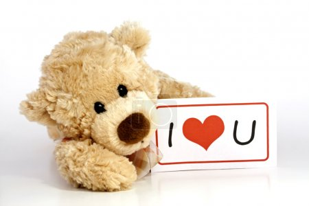 Photo pour Mignon ours en peluche brun fourrure couché tenant un I Love You signe isolé sur fond blanc avec espace de copie . - image libre de droit
