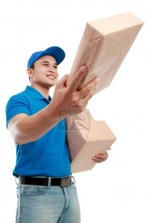 Young man courier in blue uniform with packages is...