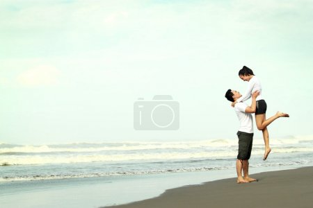 Photo for An attractive happy couple having fun on the beach - Royalty Free Image