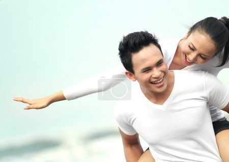 Photo for Close up portrait of a young asian man giving piggyback to woman on the beach. - Royalty Free Image