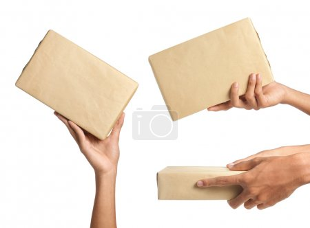 Photo for Hand holding parcel, wrapped in brown paper - Royalty Free Image