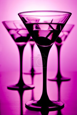 Photo for Four glasses of martini on purple background, shallow depth of field - Royalty Free Image