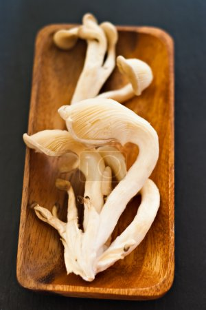 Oyster mushrooms in wood tray on black...