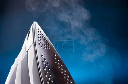 Photo pour Gros plan de l'outil de repassage émettant de la vapeur sur bleu - image libre de droit