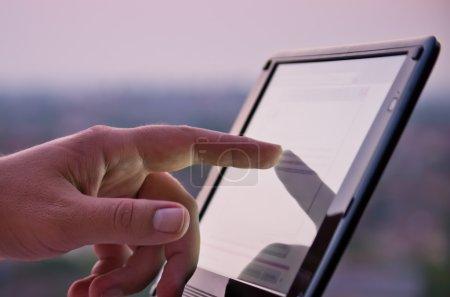 Photo pour Gros plan de l'écran tactile de la main sur tablette-PC avec une faible profondeur de champ - image libre de droit
