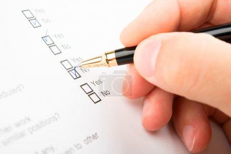 Photo pour Remplissage du questionnaire une personne par un stylo bille - image libre de droit