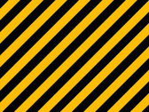 Yellow and black diagonal hazard stripes painted on old brick wa