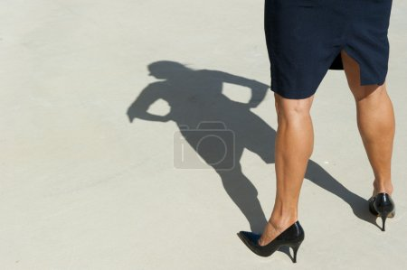 Photo for Sexy high heel legs of confident, determined, dominant and successful woman, visible in isolated shadow on the concrete floor outdoor, with lots of copy space. - Royalty Free Image