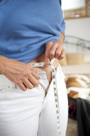 Woman on diet with measuring tape around waist