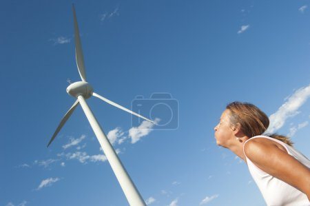 Renewable energy power wind mill and pushing woman
