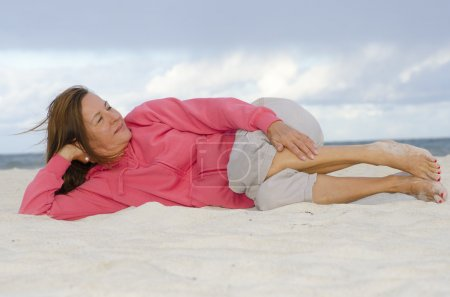 Attractive mature woman relaxed, happy at beach