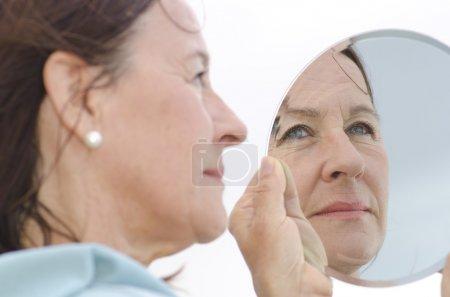 Portrait mature woman in mirror