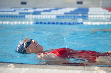 Photo for Happy and fit senior woman enjoying active retirement with exercising in swimming pool. - Royalty Free Image