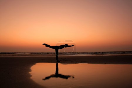 A man silhouette in a yoga warrior pose on a sunset seashore background