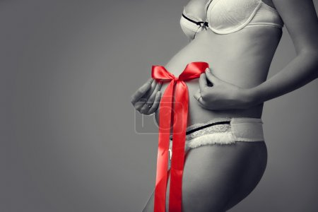 Black and white photos of pregnant belly with a red bow in his h