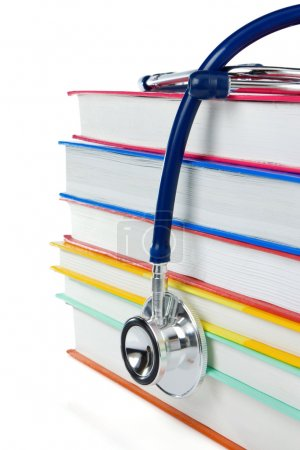 Pile of books and stethoscope isolated on white