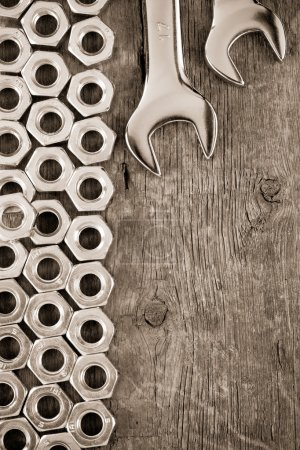 Metal nuts and wrench tool on wood background