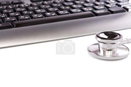 Stethoscope at keyboard isolated on white