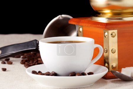 Coffee, beans, cup, pot and grinder on sacking