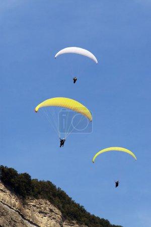Photo pour Trois parapentes flottent en formation au-dessus d'une montagne contre un ciel bleu clair . - image libre de droit