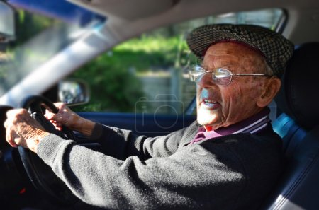 Photo for A very old man with a valid driving license drives a car. - Royalty Free Image