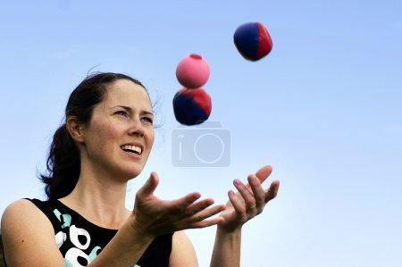 Young woman juggler is juggling balls....