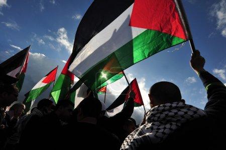 Photo pour Silhouette d'hommes palestiniens brandissant le drapeau palestinien - image libre de droit