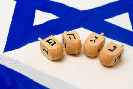 Photo pour Un drapeau israélien blanc et bleu avec l'étoile de David dessus avec des dreidels en bois pour la fête juive de Hanoukka . - image libre de droit