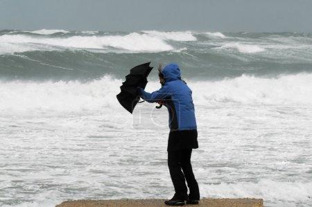 Photo pour Une femme en imperméable bleu tenant un parapluie noir lutte avec le parapluie en raison du temps orageux et venteux sur une plage - image libre de droit