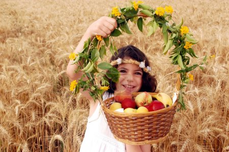 Girl Holds Basket of Fruit in Field of Wheat