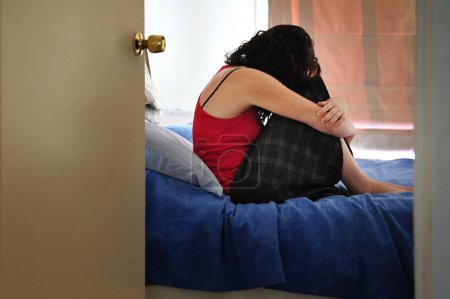 Photo for Depressed young woman sitting on the bed at home suffering from a severe depression - Royalty Free Image