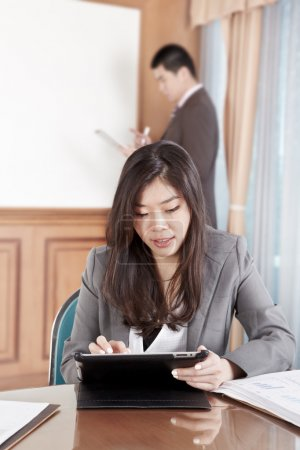 Photo for Chinese businesswoman busy working with her tablet while businessman on background busy preparing presentation - Royalty Free Image