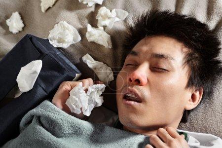 Photo pour Un homme malade dormant avec beaucoup de tissu utilisé autour de lui - image libre de droit