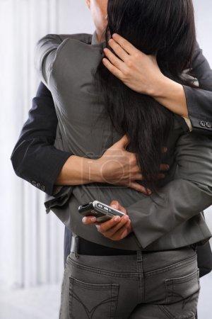 Photo pour Couple d'affaires câlin et embrasser encore la femme qui utilise toujours le téléphone cellulaire secrètement, peut être concept pour un mode de vie occupé de tricherie - image libre de droit