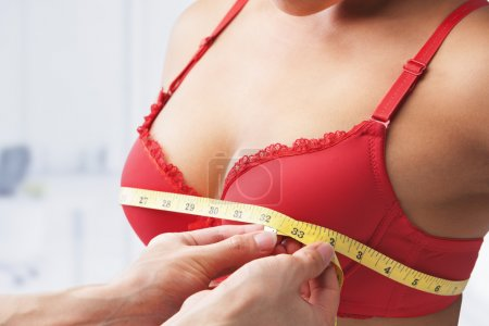 Photo for Measuring bust size of woman wearing red bra - Royalty Free Image