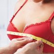 Measuring bust size of woman wearing red bra...