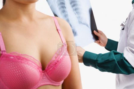 Doctor examine xray with woman on pink bra