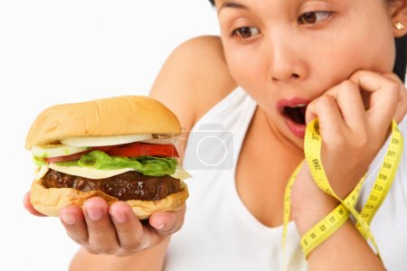 Young female surprisingly looking at burger