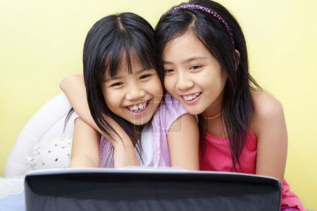 Photo for Little girls using laptop in their bedroom - Royalty Free Image