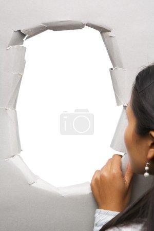 Photo pour Femme furtivement à travers le trou dans le mur - blank un, vous pouvez le plein avec image - image libre de droit