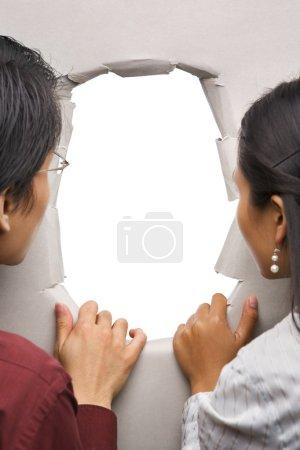 Photo pour Couple furtivement par trou dans mur - un vide, vous pouvez le plein avec image - image libre de droit